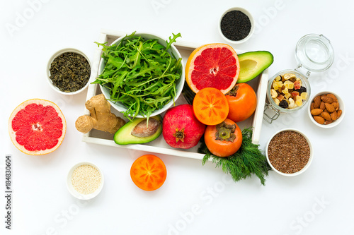 Healthy food in wooden tray: fruits, vegetables, seeds and greens on white background. Flat lay. Top view