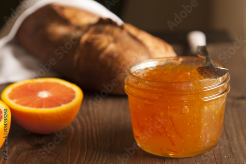 Photo Loaf of rustic artisan bread with a jar of orange marmalade