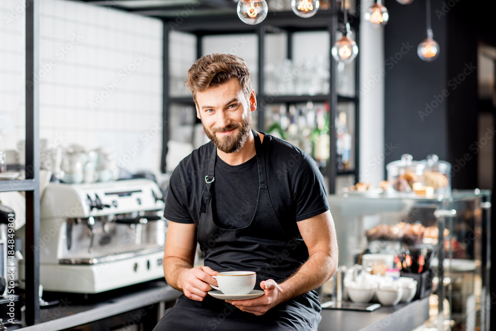 Fototapeta Portrait of a handsome barista sitting with coffee at the bar of the modern cafe interior