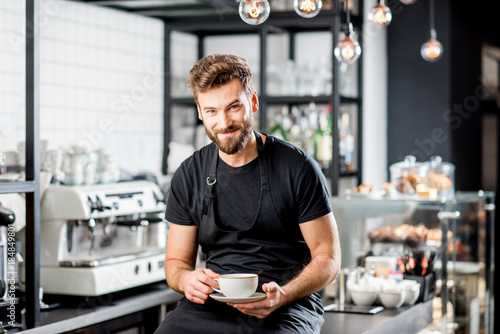 Photo Portrait of a handsome barista sitting with coffee at the bar of the modern cafe