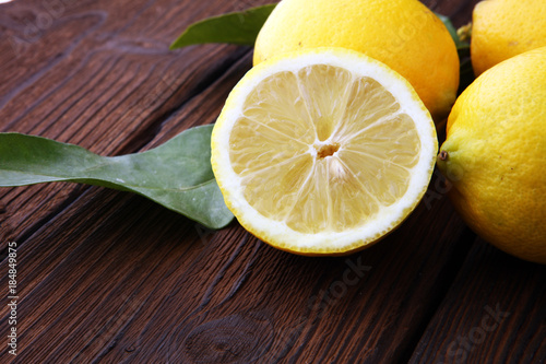 Pile of lemons with leaves on brown wooden table