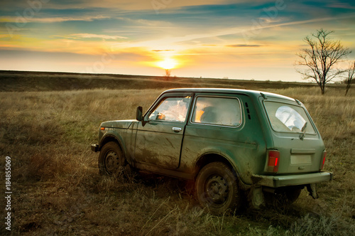 Fototapeta dirty SUV in the evening in the field obraz na płótnie