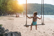 Little kids swinging with tropical beach on background