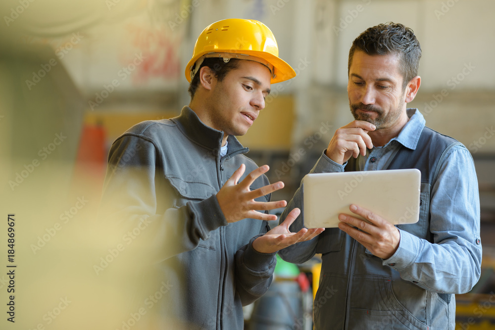 Fototapeta boss and worker checking results on the tablet