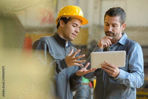 Foto  boss and worker checking results on the tablet