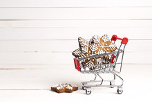 Shopping Trolley With Gingerbread Snowflakes And Cope Space On White Wooden Background.
