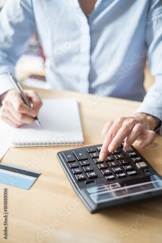 Photo Closeup of Person Writing and Using Calculator