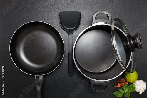 Top view frying pan and pot on black table.