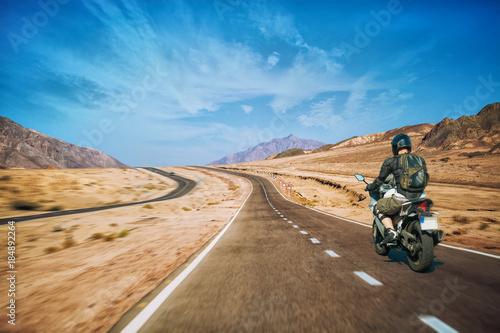 Valokuvatapetti Motorcyclist rushes along the picturesque desert mountain highway