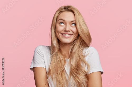 Photo  Cheerful blonde female looks upwards, has shining smile, thoughtful expression, dressed in casual white t shirt, isolated over pink studio background
