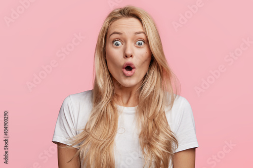 Photo  Pretty blonde woman stares at camera, keeps mouth widely opened, dressed in casu