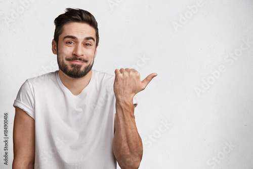 Good looking young bearded male looks with hesitant expression as doubts what to Wallpaper Mural