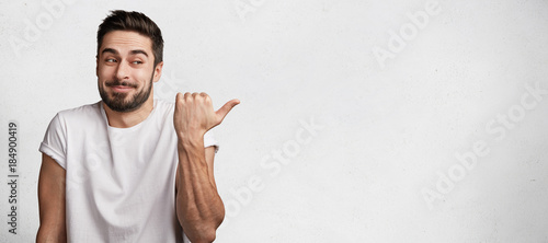 Obraz Horizontal portrait of cheerful hesitant male with thick beard and mustache wears casual t shirt, indicates with thumb aside, stands against white concrete background, copy space for advertising - fototapety do salonu