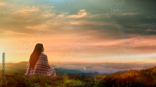 Fotografía  Young asian woman sitting alone outdoor with wild forest mountains on background