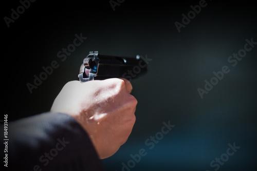 Fotografía  A man shoots a pistol. Shallow depth of field. Close-up.