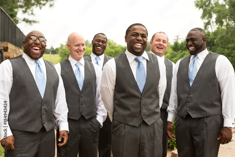 Fototapety, obrazy: Groom and groomsmen smiling at a wedding.