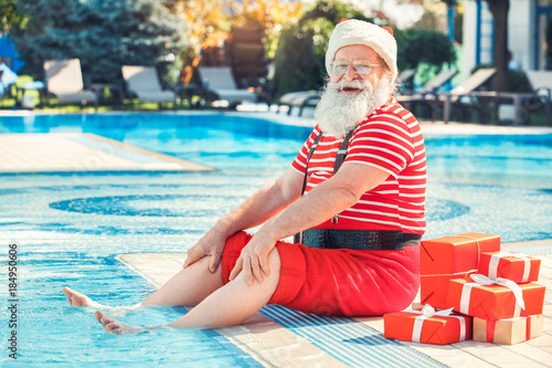 Foto  Santa Claus near the pool holiday vacation concept
