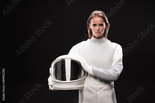 Cuadros en Lienzo Portrait of confident young female cosmonaut wearing hyperbaric astronaut protective suit is standing and looking at camera seriously while holding helmet