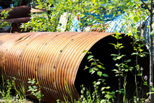 A Rusty Culvert Laying In A Scape Metal Yard