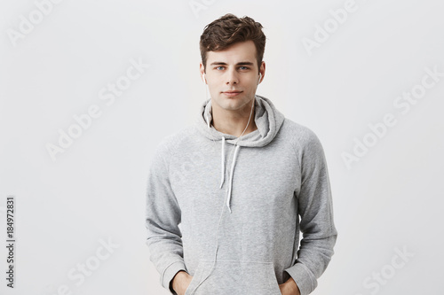 Fotografia  Handsome attractive European man in gray hoodie, with hands in pockets, look pleased at camera, has good mood as comes home after work