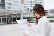 Portrait of attractive young Asian business woman analyzing charts or paperwork at outside office.