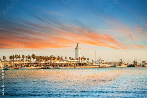 Evening panoramic aerial top view to a promenade with palms, shops and yachts and a lighthouse by the sea with dramatic colorful evening sunset sky at the background. Holiday vacation by the sea.