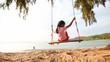 4K Asian little girl playing swing on the beach with evening ambient light and sound