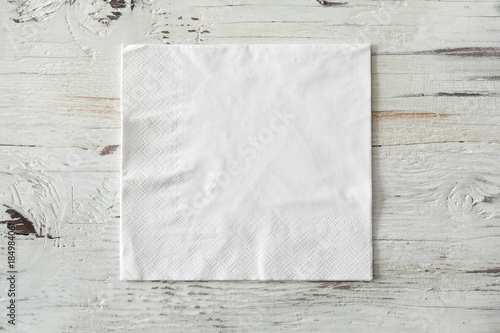 Fototapeta White paper napkin on wooden background