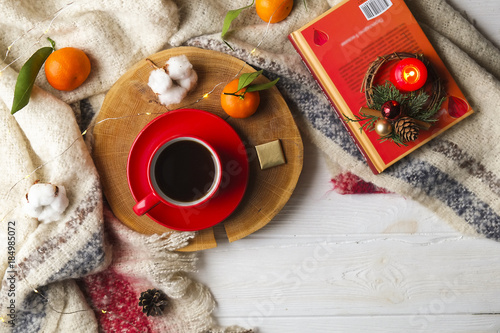 Top view red coffee cup on wooden cut with winter essentials clementine mandarin, plaid, book and glowing christmas lights on the white wooden window sill. Christmas, holiday morning comfort concept
