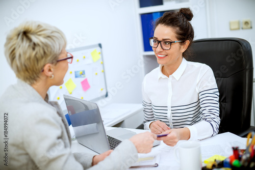 Fototapety, obrazy: Close up of focused professional satisfied woman worker taking bank card from female customer in the office.