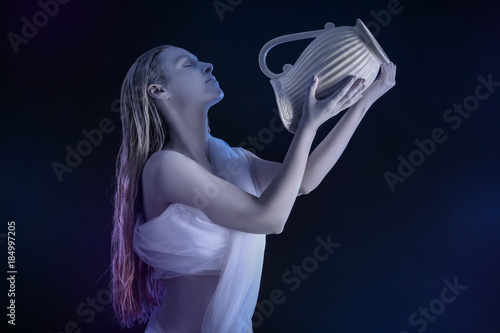Beautiful young woman with amazing body-art as Aquarius against dark background. Zodiac signs concept
