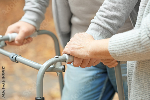 Fotografía Elderly woman and her husband with walking frame outdoors, closeup