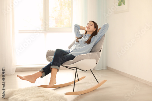 Deurstickers Ontspanning Young woman resting in rocking chair at home