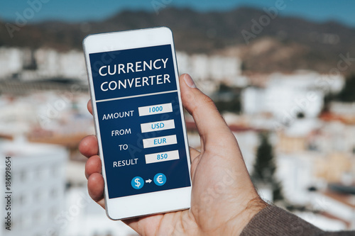 Man hand holding mobile phone with Currency converter app in the