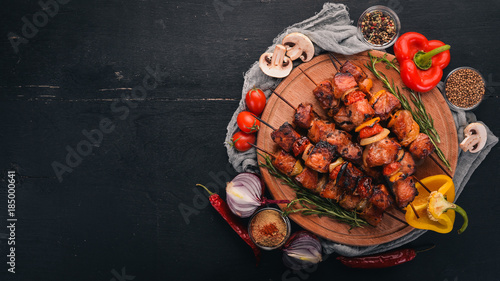 Fotomural Shish kebab on skewers with onions. On the black wooden table.