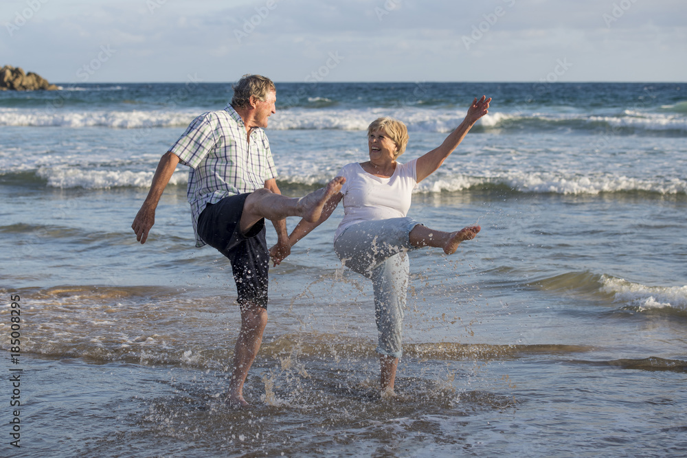 Fototapeta lovely senior mature couple on their 60s or 70s retired walking happy and relaxed on beach sea shore in romantic aging together