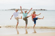 canvas print picture - group of three senior mature retired women on their 60s having fun enjoying together happy walking on the beach smiling playful