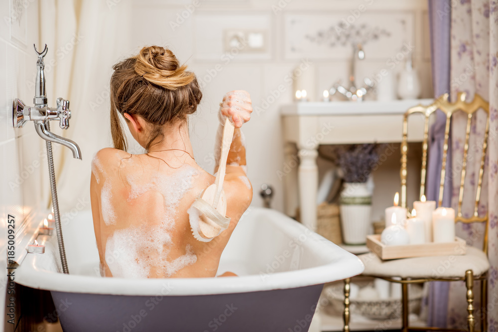 Fototapeta Young woman washing with brush in the beautiful vintage bath full of foam in the bathroom decorated with candles
