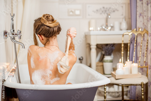 Photo Young woman washing with brush in the beautiful vintage bath full of foam in the