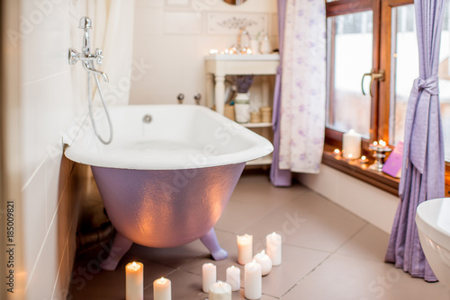 Beautiful bathroom interior with retro violet bath decorated with candles Canvas Print