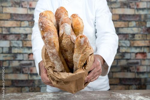 Valokuvatapetti baker holding traditional bread french baguettes