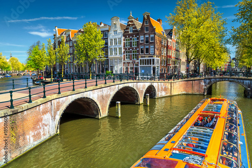 Photo  Typical Amsterdam canals with bridges and colorful boat, Netherlands, Europe