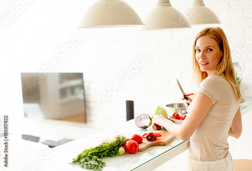 Fotobehang Koken Pretty young woman preparing healthy meal in the kitchen