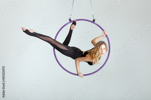 Fotografie, Obraz  Woman aerial acrobat performs with tricks on the hula hoop at the top