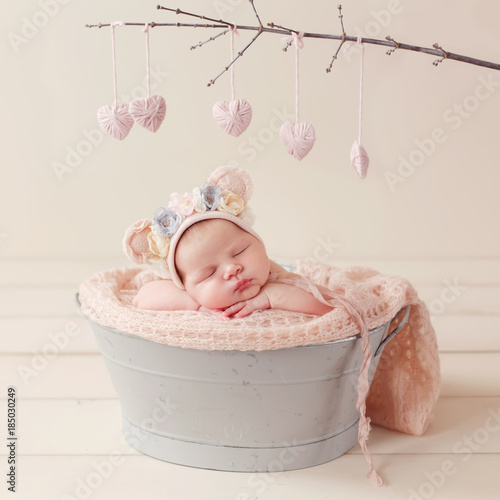 sleeping newborn in the basket, in the bear's cap, valentine's day, pink