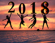 Happy new year card 2018. Silhouette young woman jumping on tropical beach over the sea and 2018 number with sunset background.