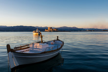 A Small Wooden Boat In Nafplio, Greece With Bourtzi View On The Background At Sunset