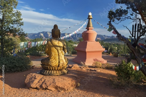 Fotografie, Tablou Amitabha Stupa, Buddha Statue and Prayer Flags with Distant Red Rock Landscape i