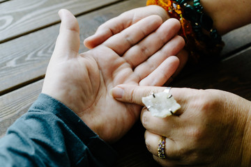 Top view of human hand and psychic or fortune teller explains lines on palm. Palmistry