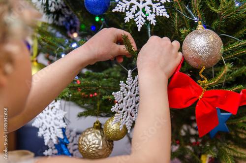 Dziewczynka wiesza ozdoby na choinkę bożonarodzeniową. Billede på lærred